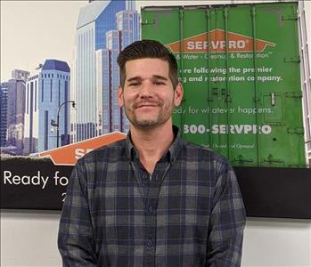 Servpro of Middletown sharing picture of their rebuild manager in front of SERVPRO Ad.